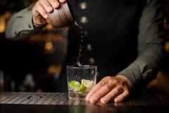 Barman que adiciona o açúcar de bastão no vidro de cocktail processo de Foto de Stock Royalty Free