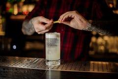 Barman que adiciona o suco do entusiasmo alaranjado a um cocktail de Gin Fizz imagens de stock royalty free