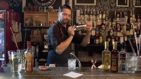 Barman que agita a garrafa que prepara bebidas na barra filme