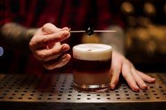 Barman que decora o cocktail doce alcoólico flocoso com uma cereja foto de stock