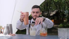 Barman que derrama lentamente o licor no vidro de vinho preparado, trabalhador da barra que prepara o cocktail através do filtro video estoque