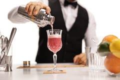 Barman que derrama seu cocktail da assinatura em um vidro imagens de stock royalty free