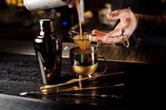 Barman que derrama um cocktail alcoólico no copo de cobre imagem de stock royalty free