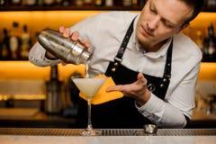 Barman que derrama uma bebida alcoólica fresca no vidro de cocktail foto de stock