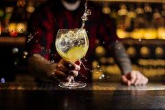 Barman que faz o respingo de um cocktail delicioso de Gin Tonic com l imagem de stock