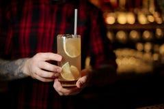 Barman que guarda um vidro do cocktail alaranjado alcoólico fresco foto de stock royalty free