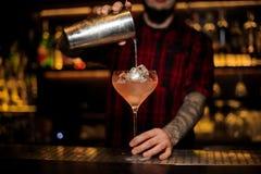 Barman que pourring um cocktail siciliano do tônico do shak de aço imagens de stock