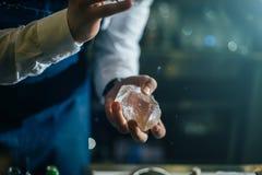 Barman que trabalha profissionalmente com gelo foto de stock royalty free