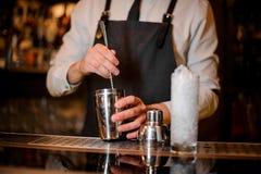 Barman remuant une boisson alcoolisée dans le dispositif trembleur en acier Image libre de droits