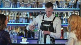Barman robi koktajlowi przy barem odpierającym dla dwa dziewczyny Zdjęcia Royalty Free