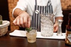 Barman robi koktajlowi przy baru kontuarem, stonowanym Obrazy Stock