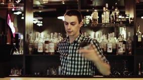 Barman robi zadziwiać sztuczki z dwa szkłami, stoi za barem zbiory