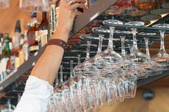 The waiter takes a bottle of whiskey. The barman`s hand gives a bottle of whiskey from the bar shelf. Glasses of wine in the foreground Stock Photography