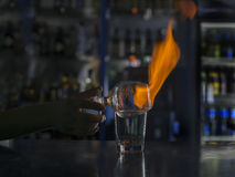 Barman`s hands in bar interior making alcohol flaming cocktail. Professional bartender at work in bar mixing drink with. Burning fire stock image