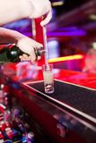 Barman's hands in interior bar are poured liquor Royalty Free Stock Image