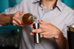 Barman's hands making shot cocktail. Barman's hands in bar interior making alcohol shot cocktail. Professional bartender at work in bar pouring drink into stock image