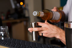 Barman's hands making shot cocktail. Barman's hands in bar interior making alcohol shot cocktail. Professional bartender at work in bar pouring drink into royalty free stock images