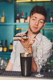 Barman&s hands making shot cocktail. Barmans hands in bar interior making alcohol shot cocktail. Professional bartender at work in bar pouring drink into stock photo