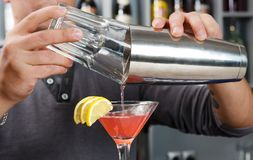 Barman's hands mixing cosmopolitan cocktail stock photos