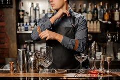 Barman se tenant derrière le compteur de barre avec un équipement de barre photo stock