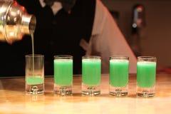 Barman servant les tirs verts d'alcool. photographie stock libre de droits