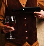 Barman serves red wine glass. Waiter pours red wine. Into glass from bottle. Male hand holds bottle of wine on beige wall background. Service and restaurant stock image