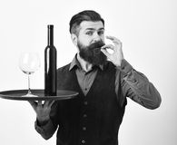 Barman serves red wine showing perfect taste sign. Waiter with glass and bottle of wine on tray. Restaurant service concept. Man with beard holds bottle with Stock Image
