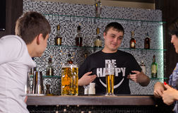Barman serving customers at the bar counter. Friendly young male barman serving customers at the bar counter smiling and gesturing with his hands as he chats to Stock Photos