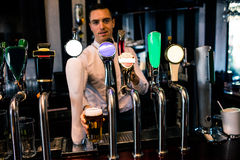 Barman serving a pint of beer Stock Photo