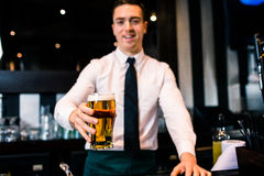 Barman serving a pint of beer Stock Photography