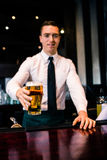 Barman serving a pint of beer Royalty Free Stock Photography