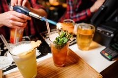 Barman sets fire to sprig of mint on orange-colored cocktails. With ice using bar equipment Royalty Free Stock Photography