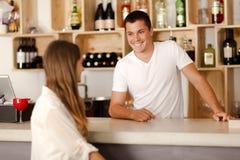 Barman smiling at female customer. Young barman smiling at female customer in a bar Royalty Free Stock Photography