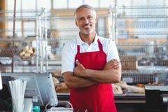 Barman souriant à l'appareil-photo avec des bras croisés Image stock