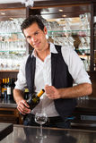 Barman standing behind bar with wine Stock Photos