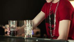 Barman stawia jagody w szkło i miażdży one zbiory