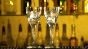 Barman stawia sześciany lód w szkło, nalewać zbiory