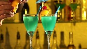 Barman stawia sześciany lód w szkło, nalewa zbiory