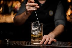 Barman stirring a delicious cocktail with a steel spoon in the measuring glass cup. On the bar counter in the dark blurred background stock photography