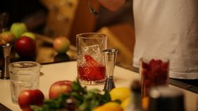 Barman stirs a thin spoon with a cocktail in a glass with ice stock footage