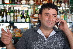 Barman talks by phone. Smiling man against shelves with bottles Royalty Free Stock Images