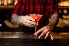 Barman with tattoos holding a fresh sweet alcoholic cocktail. Decorated with orange fruit on the bar counter stock photography