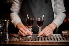 Barman tenant deux cocktails red delicious sur le compteur de barre photo libre de droits