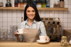 Barman tenant deux tasses de café image libre de droits