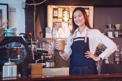 Barman tenant la tasse et les sourires de café en son café Photo libre de droits