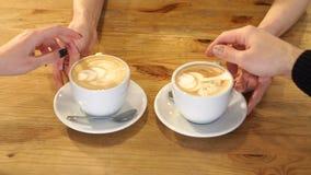 Barman tenant le cappuccino deux aromatique, les servant aux visiteurs de café banque de vidéos