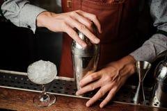 Barman tenant un dispositif trembleur dans des mains derrière le compteur de barre Images stock