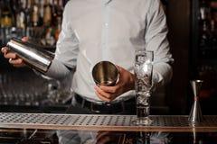 Barman tenant un dispositif trembleur de cocktail au compteur de barre Photo stock