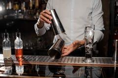 Barman tenant un dispositif trembleur de cocktail en acier au compteur de barre Image libre de droits