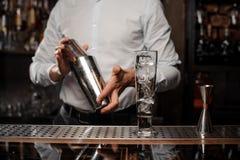 Barman tenant un dispositif trembleur en acier au compteur de barre Photographie stock libre de droits